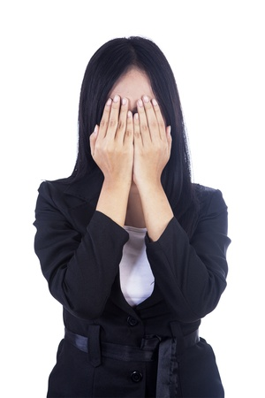 cautious: Beautiful businesswoman is covering her face isolated in white