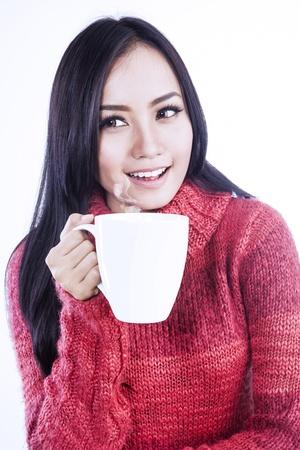 mujer tomando cafe: Hermosa mujer disfruta de una taza de té en el estudio