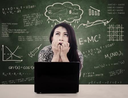 nerveux: Belle fille est nerveux alors qu'elle étudiait en face de son ordinateur portable