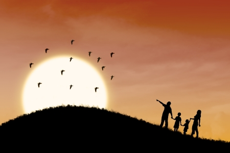 Silhouette of happy family walking up the hill with sunset scene photo