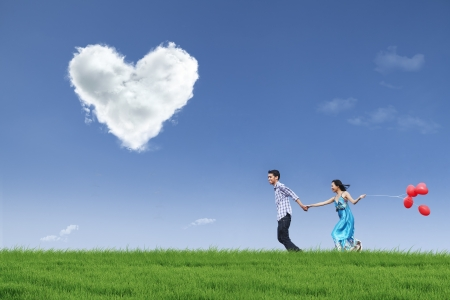 asian couple happy: Happy couple is running together in green field while holding red balloons