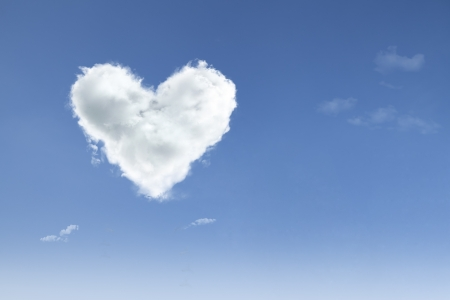 Love cloud with heart shape floating on blue sky photo