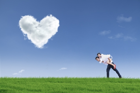 A guy is giving his girlfriend a piggyback ride in green field during Valentines day photo