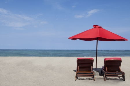 Two red umbrella beach and chairs in paradise island photo