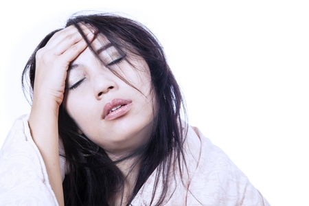 Woman is having bad headache by rubbing her forehead, isolated in white photo