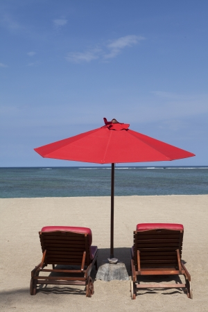 Tropical beach with two red umbrellas photo