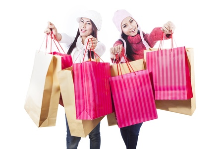 Two friends are holding shopping bags in winter clothes, isolated in white Stock Photo - 16634147