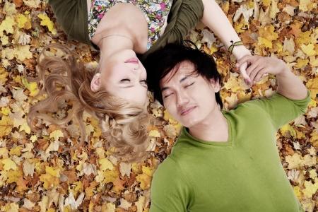 jovenes enamorados: Pareja acostada en las hojas de otoño, mientras que la celebración de su mano Foto de archivo