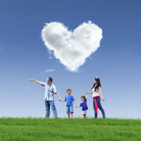 Happy family taking a stroll in the park under love shaped cloud photo