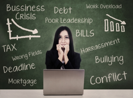 Beautiful businesswoman in front of a laptop worry about the debt crisis Stock Photo - 16660495