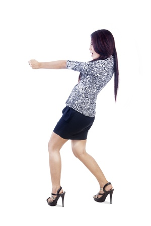 Businesswoman is pulling something on copyspace using strength expression photo