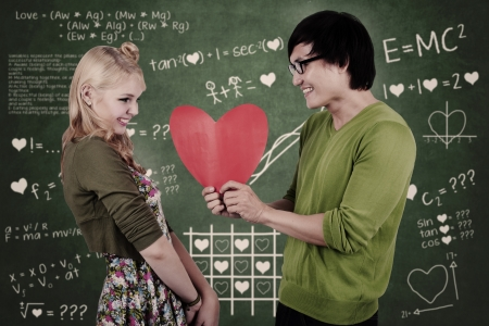 goofy: Cute nerd couple holding red heart in the classroom