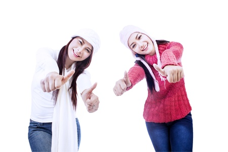 thumbs up group: Two sisters are excited upon successful project, isolated in white Stock Photo