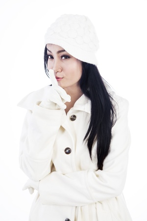 Portrait of beautiful woman wearing winter clothes gesturing to be quiet  isolated on white Stock Photo
