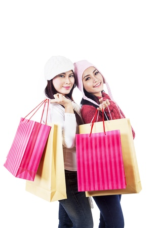 Two friends are shopping together, carrying many bags in white background photo