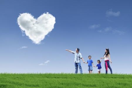 familia en jardin: La familia feliz est� caminando en el parque para ver las nubes del amor