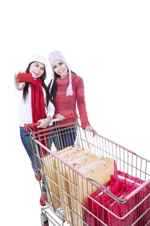 Two friends are shopping with trolley in winter time, isolated in white photo
