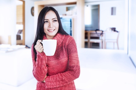 Beautiful happy smiling woman dressed with winter clothes holding a hot cup of coffee at home photo