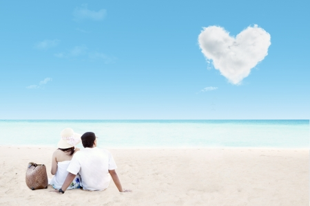 honeymoon couple: Beautiful couple by the beach with clouds of heart