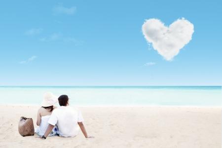 luna de miel: Hermosa pareja en la playa con las nubes del coraz�n