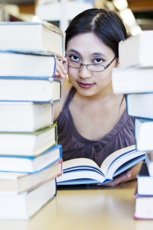 Beautiful female student studying at the library surrounded with books photo
