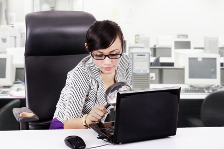 ibook: Business woman with magnifying glasses and laptop at office