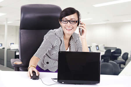Beautiful business executive is on the phone while working with her laptop Stock Photo - 16684393