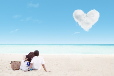 Enjoying honeymoon at white sand beach with love cloud photo