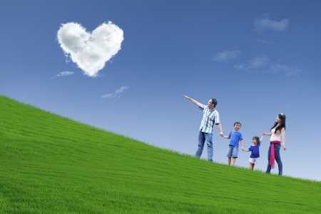 under heart: Family stroll in park under heart clouds