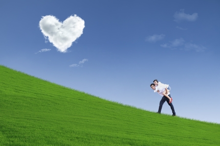 under heart: Girl on piggyback ride under heart clouds Stock Photo