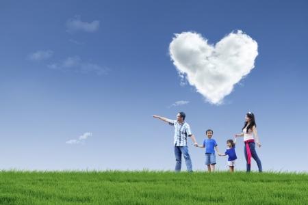 가족: 하늘에 사랑의 구름과 함께 공원에서 산책 행복한 가족