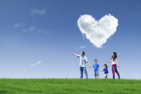 felicidad: Familia feliz caminando en el parque con la nube de amor en el cielo Foto de archivo