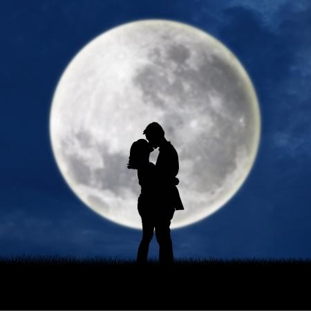 Gros plan d'un couple s'embrassant sur la silhouette pleine lune la nuit