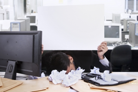 Young businessman with his face down while holding a white copyspace at his office photo