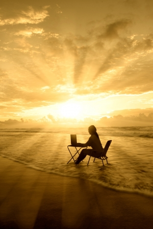 Silhouette of woman study on the beach under beautiful rays of light photo