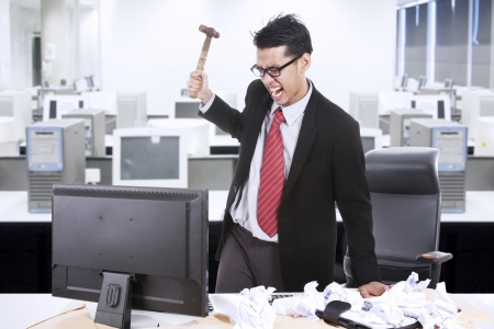 messy office: Angry businessman is about to throw a hammer at his computer in the office