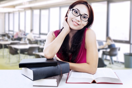 scholarship: Young female student study at the library surrounded with books