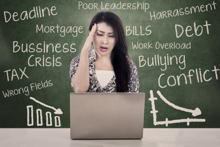 fearing: Beautiful woman sitting in front of her laptop fearing for debt and crisis