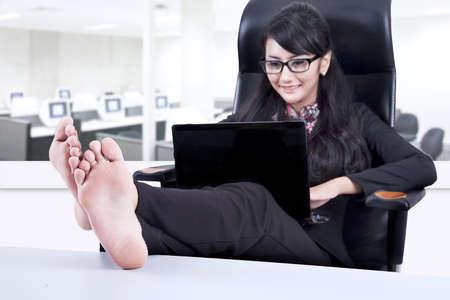 office break: Hermosa empresaria pelo largo poner las piernas en alto durante el descanso de la oficina Foto de archivo