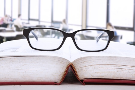 Picture of an open book with a glasses on top of it photo