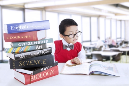 Smart boy with glasses study different literature in the library photo