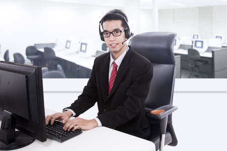 Young businessman is smiling to offer customer service in his office photo