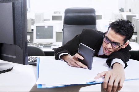 A businessman is holding a calculator worrying about paying bills and making profit photo