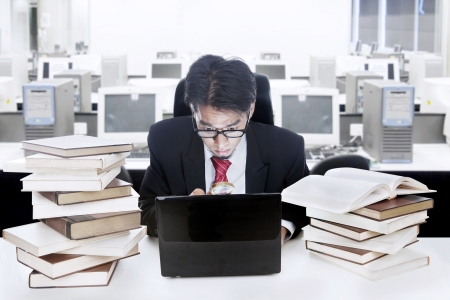 Young businessman is reading something at his laptop with shock surrounded with lots of books photo