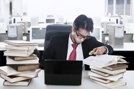 Businessman holding a clock surrounded with books and laptop in his office photo