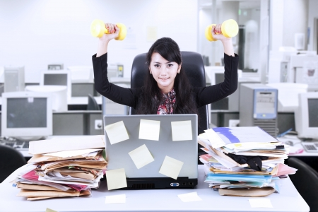 office wear: Young businesswoman doing exercise in front of her laptop with lots of sticky notes