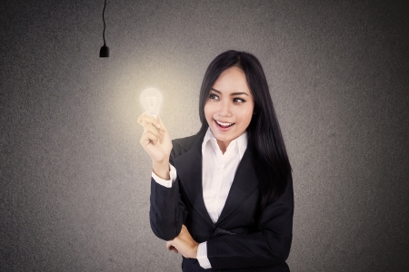 Businesswoman smiling because she got one lit light bulb Stock Photo - 16823450