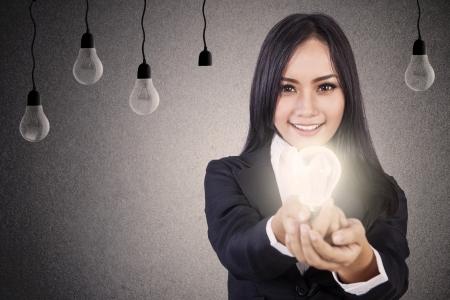 Empresaria que da una bombilla brillante idea brillante que simboliza Foto de archivo - 16823446