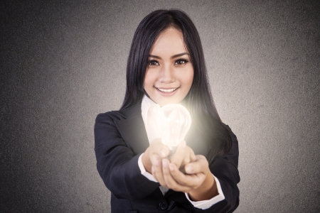 Businesswoman is smiling while giving a lit light bulb photo