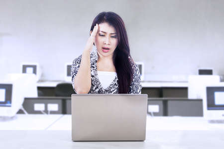 Businesswoman stress out while working with her laptop in office photo